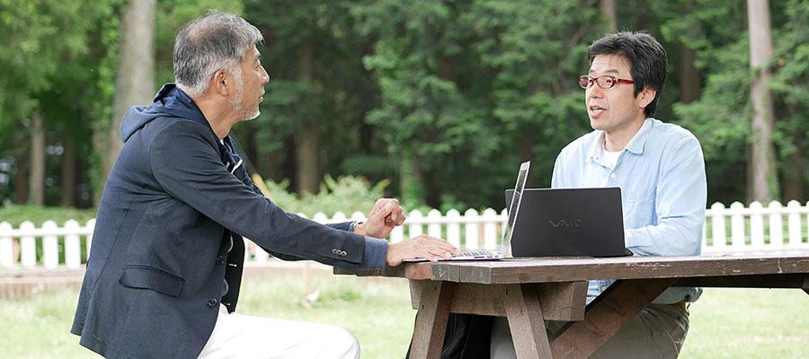 椅子に座って話す桑名さんと塚本